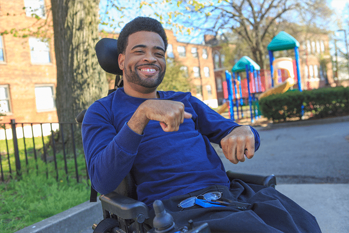 African American man in electric wheelchair sitting outside smiling