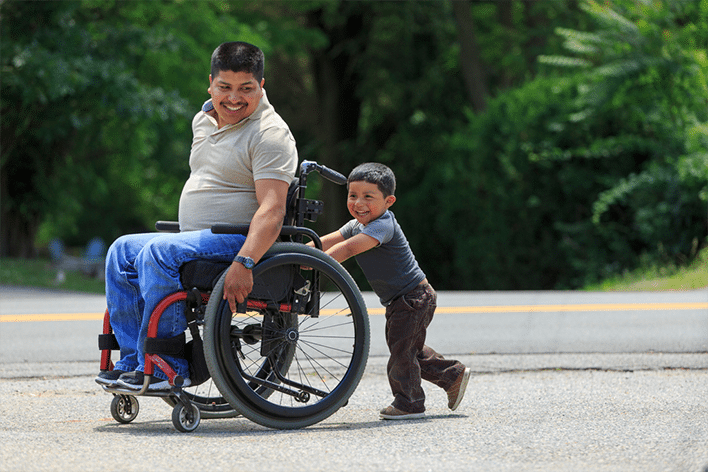 Small child pushing disabled hispanic father in wheelchair